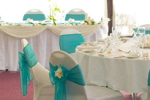 Beautiful tables with aqua chair ties and frangipani